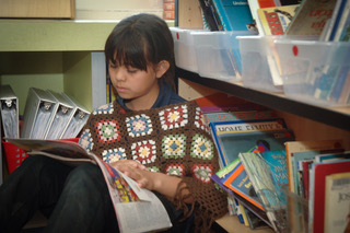 Student reads a book in a library